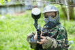 Paintball player in camouflage uniform and protective mask poses