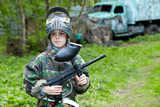 Boy in camouflage stands against the paintball area