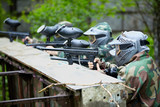 Four paintball players in camouflage and protective masks aims