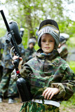 Boy in the camouflage suit holds a paintball gun barrel up