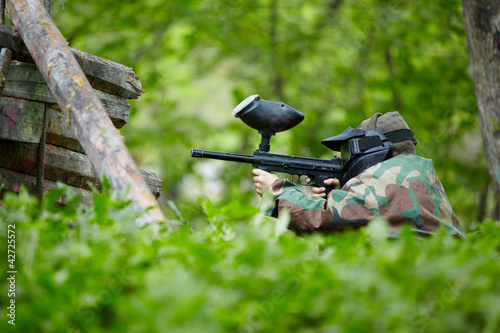 Paintball player in camouflage and protective mask
