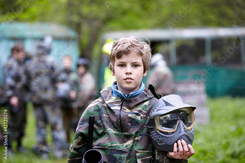 Boy in camouflage holds paintball gun barrel up in one hand