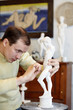Sculptor works with concentration in studio on plaster sculpture