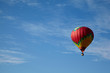 Many-colored hot air balloon with people fly in blue sky.