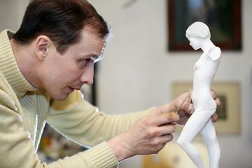 Sculptor works in studio on fragment of plaster sculpture.
