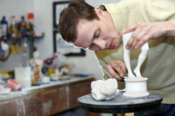 Sculptor works in studio on fragment of plaster sculpture.