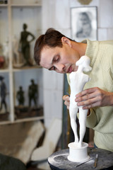Sculptor works attentively in the studio on plaster sculpture.
