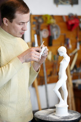 Sculptor works attentively in studio on fragment of sculpture