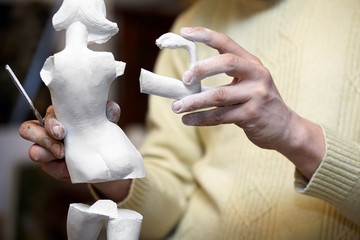 Hands of sculptor hold parts of plaster statuette.