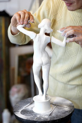Sculptor attach arms to armless plaster statuette.