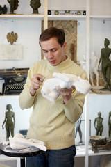 Sculptor files attentively in studio body of plaster sculpture