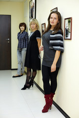 Three women stand in the hallway, leaning their backs to wall