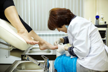 Chiropody master processes nails of client in beauty salon