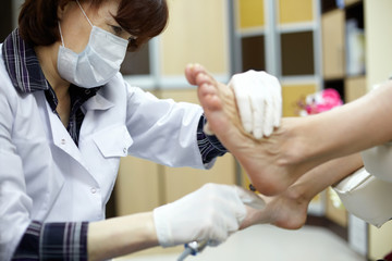 Master chiropody treats the sole skin of female client.