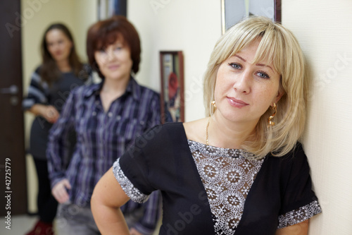Three women stand near the wall, focus on face of blonde