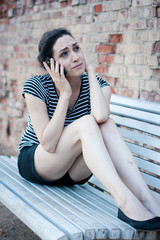Unhappy young woman crying while talking on the phone