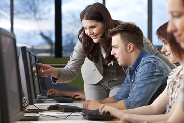 Student & Teacher Using Computers at College