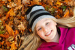 girl on autumn leaves smiling