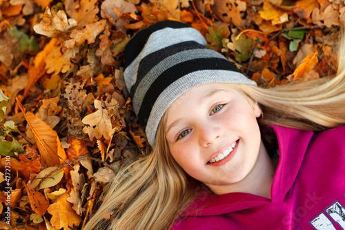 girl on autumn leaves smiling