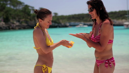 Young female friends applying sanlotion on the beach