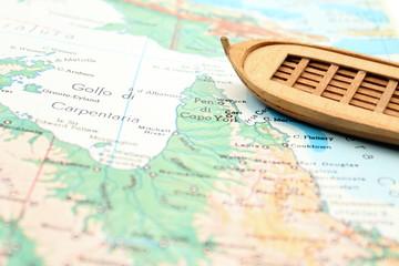 Una barca di legno su cartina enciclopedia.