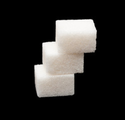 three lumps of sugar on a black background
