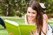 Portrait of a student reading a book on the grass