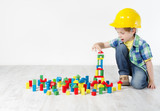 builder boy in helmt playing with toys blocks, building city