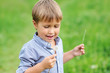 Young boy blowing dandelion