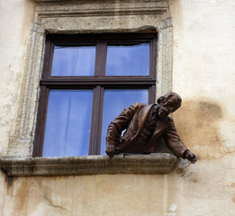 Statue of a male figure leaning out of a window