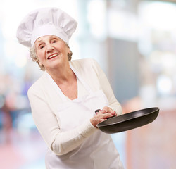 portrait of a friendly cook senior woman holding pan indoor