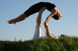 Two young man and woman couple doing yoga. Outdoors.