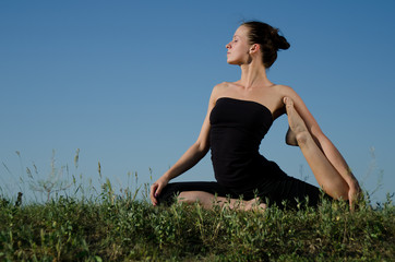 Yoga woman on green grass.  Sky background.