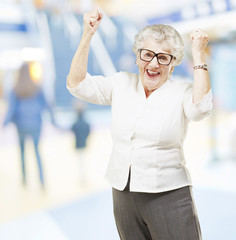 portrait of a happy senior woman doing a victory gesture at mall