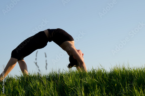 Yoga woman on green grass. Sky background .