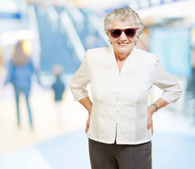 portrait of senior woman smiling and wearing sunglasses at mall