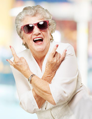 portrait of senior woman smiling and wearing sunglasses against