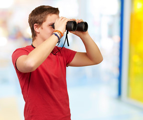 portrait of young man looking through a binoculars indoor