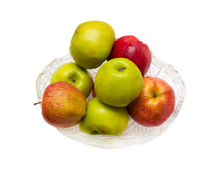 green and red apples in a crystal dish on a white background