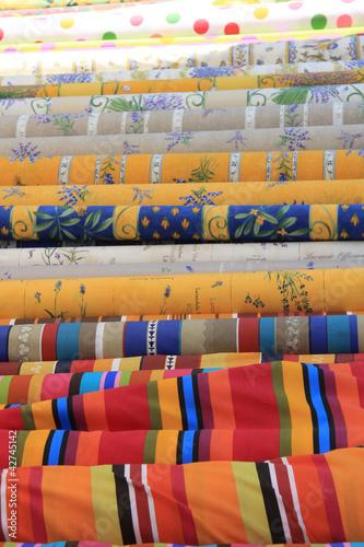 Rolls of Provencal textile on a market stall © Studio Porto Sabbia