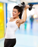 portrait of a young pretty woman holding weights and doing fitne