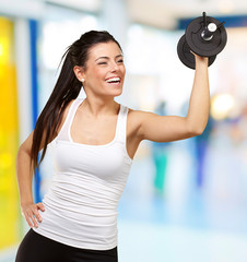 portrait of young girl training with weights at gym