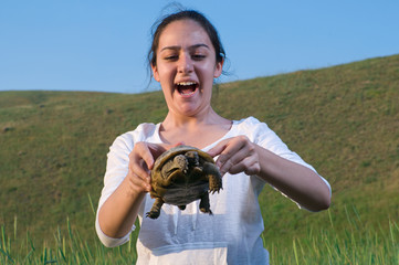 Teen girl playing with turtle at meadow.