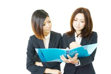書類をもち考え込む二人のオフィスレディー