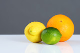 Beautiful citrus fruits in front of grey