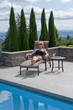 Attractive blond woman lounges by swimming pool
