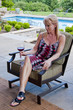 Attractive blond woman sitting on a patio holding a wine glass