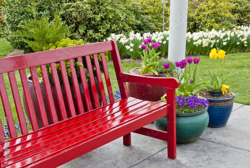 Red garden bench on patio with pots of spring flowers