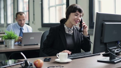 Young attractive businesswoman talking on telephone