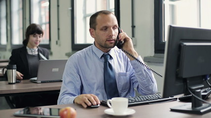 Young businessman talking on telephone in the office